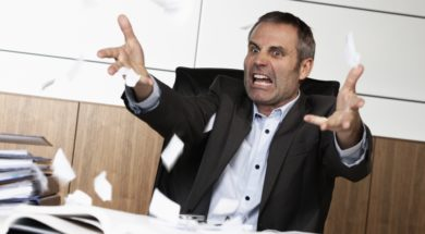 Overloaded senior businessman being upset about work, tearing pa