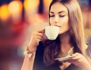 Coffee. Beautiful Girl Drinking Tea or Coffee in Cafe. Beauty Mo