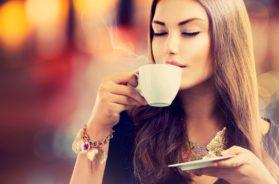 Coffee. Beautiful Girl Drinking Tea or Coffee in Cafe. Beauty Mo