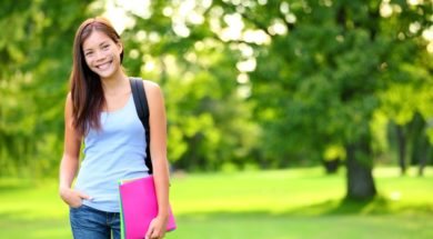 Student girl portrait holding books wearing backpack outdoor in