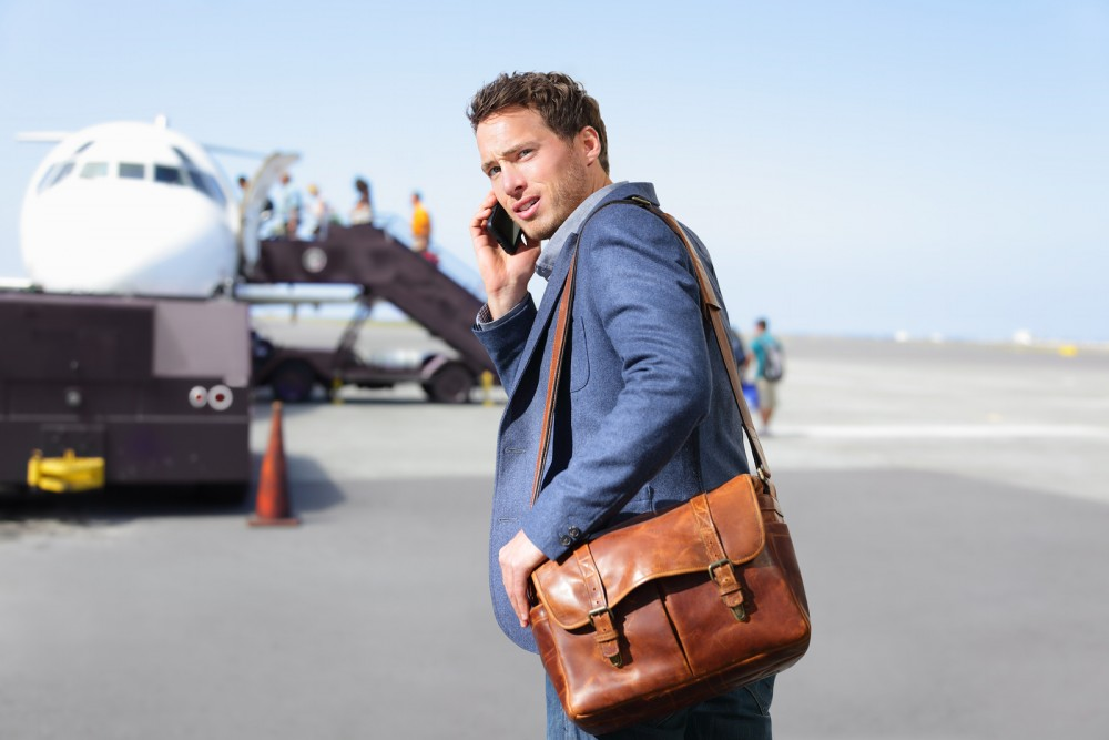 Airport business man on smartphone by plane. Young male professi