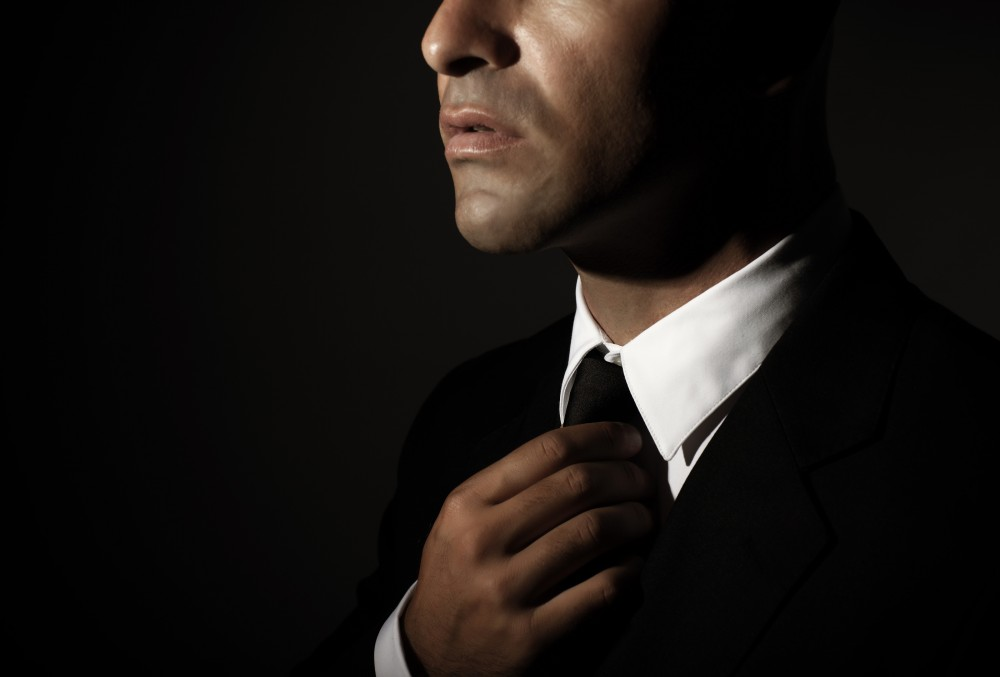 Young handsome man fixed tie isolated on black background, face
