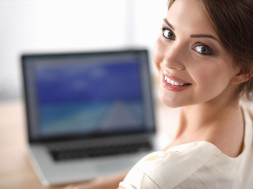 Portrait of beautiful young business woman working on a laptop a