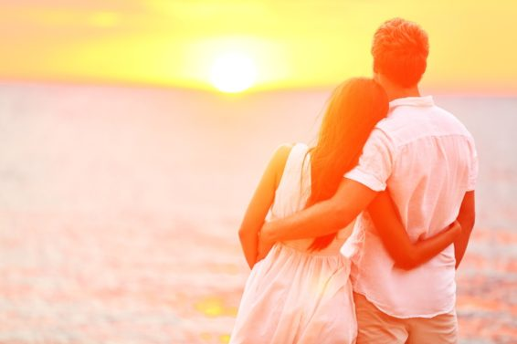 Honeymoon couple romantic in love at beach sunset. Newlywed happ