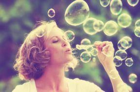 a pretty girl blowing bubbles – vintage toned with a retro insta