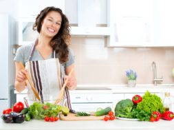 Young Woman Cooking in the kitchen. Healthy Food – Vegetable Sal