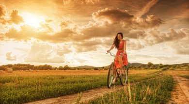 Beautiful woman with old bike in a wheat field