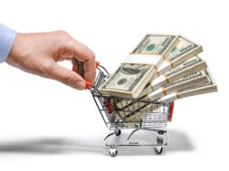 businessman's hand & steel grocery cart full of money stacks – i