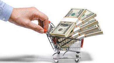 businessman's hand & steel grocery cart full of money stacks – i