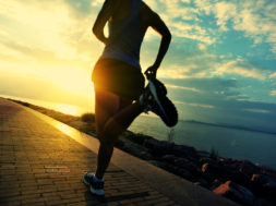 Runner athlete running at seaside. woman fitness silhouette sunr