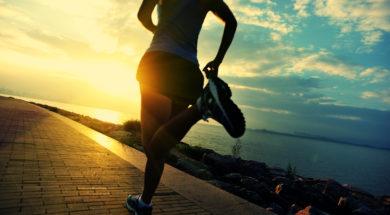 Runner athlete running at seaside. woman fitness silhouette sunr