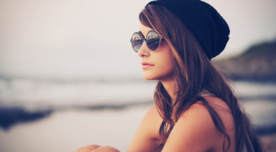 Fashion portrait of young hipster woman with hat and sunglasses